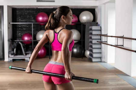 Beautiful muscular woman doing exercise with gymnastic stick at the gym. Stock Photo