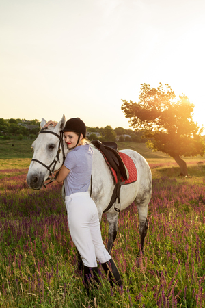 Jockey young girl petting and hugging white horse in evening sunset. Sun flare