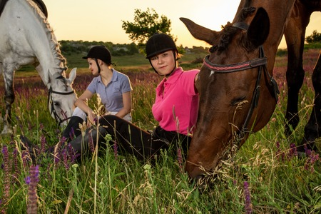 Friendly women are sitting next to a brown and white horses, which grazed in the meadow.