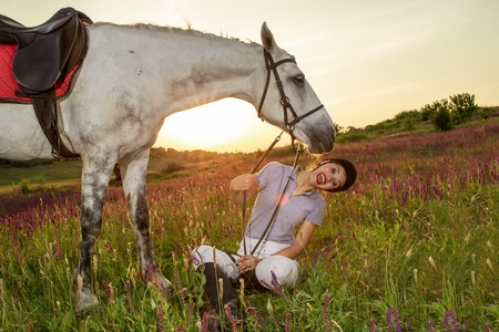 Beautiful smiling girl jockey stand next to her white horse wearing special uniform on a sky and green field background on a sunset.