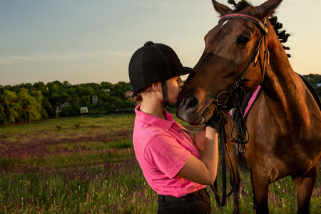 Beautiful smiling girl jockey stand next to her brown horse wearing special uniform on a sky and green field background on a sunset.