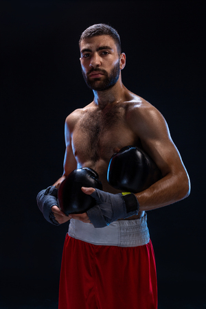 Handsome athletic guy in a red shorts on a black background. The boxer is fetching his breath after practicing hooks and blows.