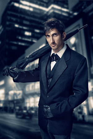 Film noir. Retro style fashion portrait of a killer. A man in a suit with an umbrella in his hand against a background of a night city