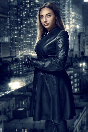 Retro portrait of inaccessible beautiful woman in black cloak stands against the background of the night city. Film noir. Vintage Hollywood style. Studio shot.