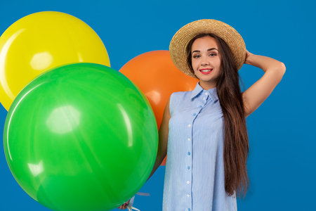 Cute brunette standing in a studio holding orange, yellow and green balloons. She wears light blue dress and has long and wavy hair.