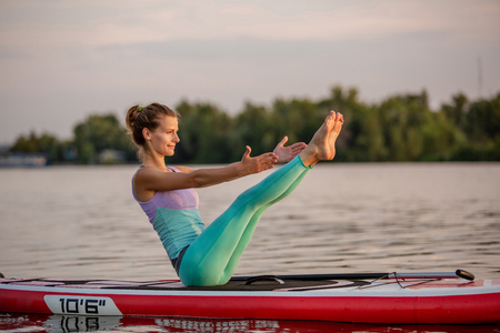 Young beautiful woman meditating in a sea at SUP paddleboarding. Healthy lifestyle.