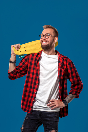 Charismatic cheerful young bearded man dressed in checkered shirt, white T-shirt and glasses, with yellow skateboard in his hands. Studio shot with blue background
