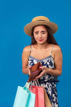 Portrait of unhappy young woman looking in her wallet in shopping center, spent too much, not enough cash, lost money, broke Banco de Imagens