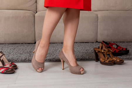 Woman in fashionable short dress skirt high heels standing nearn couch.