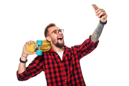 Young man holding the skateboard on shoulder raising his phone takes a selfie on a white background.