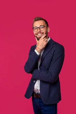 Portrait view of an attractive happy businessman with glasses on a pink background Stock Photo