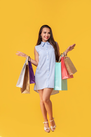 Full length photo of young woman in dress looking back on copy space and holding colorful shopping packages over yellow background