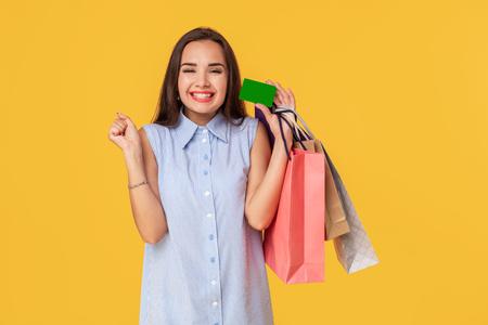 Trendy vrouw 20s in jurk met lang bruin haar glimlachend terwijl verschillende winkelpakketten en kaart in handen geïsoleerd op gele achtergrond Stockfoto
