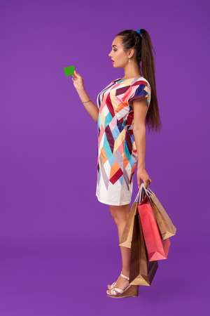 Attractive woman 20s in dress holding shopping packages and showing green credit card isolated over purple background