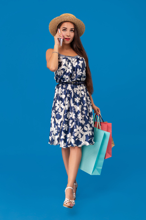 Shopping concept. Beautiful smiling brunette with shopping bags talking on the phone on blue studio background with copy space. Stock fotó