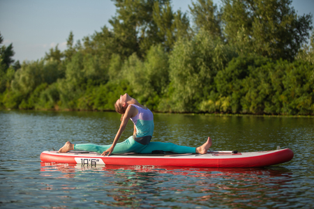 Young woman doing yoga on sup board with paddle. Meditative pose, side view - concept of harmony with the nature