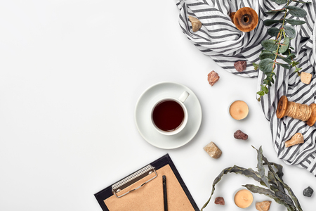 Cup with a ready tea on a white table. Top view, flat lay. Copy space. Still life