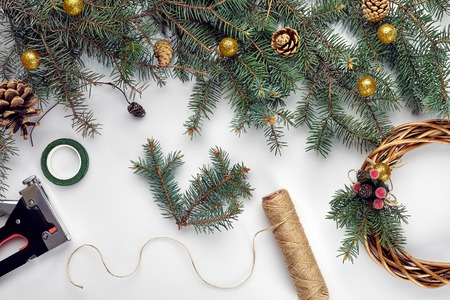 Creative christmas diy. Woman making handmade xmas wreath. Home leisure, tools, trinkets and details for holiday decorations on white table background. Top view