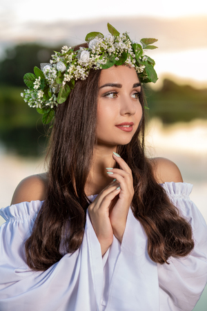 Woman in white dress in the water. Art Woman with wreath on her head in river. Wet witch Girl in the lake, mystical mysterious woman. Wreath on her head, Slavic traditions and paganism Stock Photo