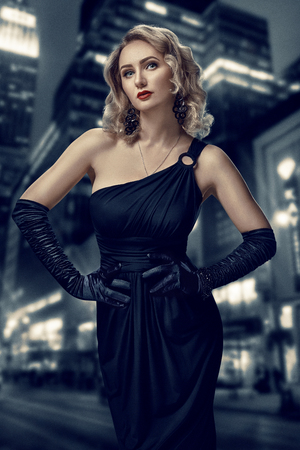 Retro portrait of inaccessible beautiful woman in black dress with red lips, smokey eyes and long earrings stands against the background of the night city. Film noir. Vintage Hollywood style. Stock Photo