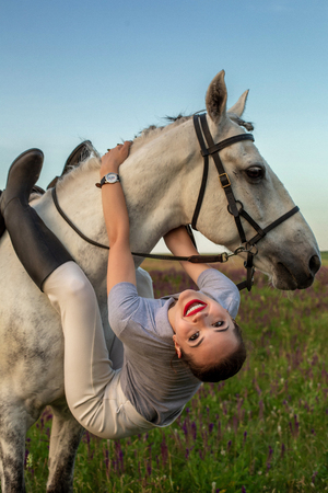 Beautiful young girl smile at her horse dressing uniform competition: outdoors portrait on sunset Reklamní fotografie