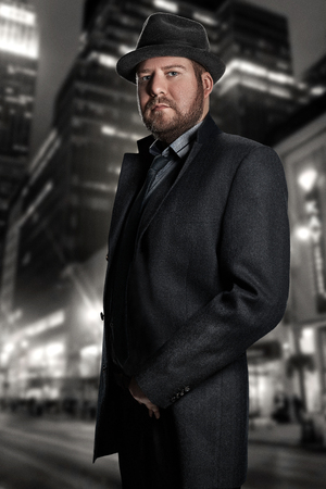 Film noir. Retro style fashion portrait of a detective. A man in a suit against a background of a night city Stock Photo
