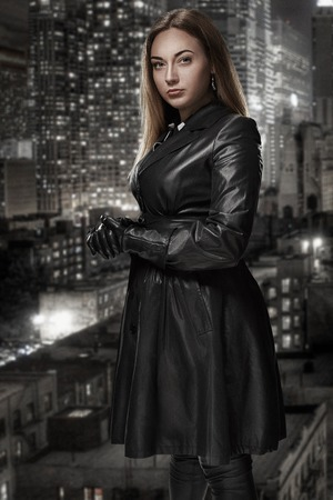 Retro portrait of inaccessible beautiful woman in black cloak stands against the background of the night city. Film noir. Vintage Hollywood style. Studio shot. Stock Photo