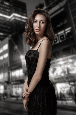 Retro portrait of inaccessible beautiful woman in black dress stands against the background of the night city. Film noir. Vintage Hollywood style. Studio shot. Stock Photo