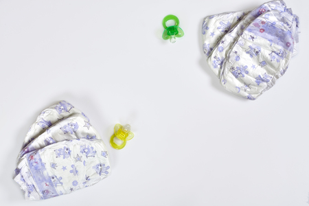 Babies goods diaper, soother or nipple on white background with copy space. Top view or flat lay.