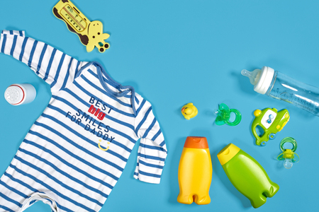 Baby care with bath set. Nipple, toy, clothes, shampoo on blue background top view mockup