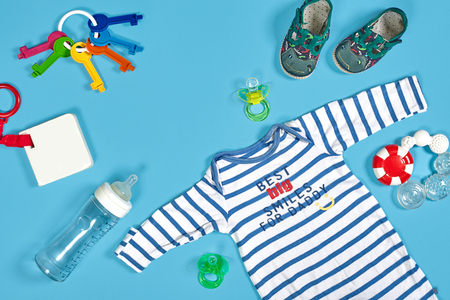 Baby clothing, toiletries, toys and health care accessories on blue background.