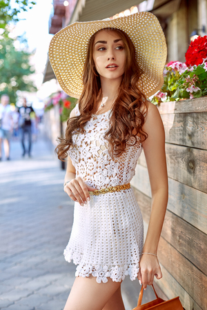 Young stylish woman walking on the street, wearing trendy outfit, straw hat, travel with backpack.