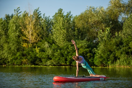 Photo of young woman doing hand stand on stand up paddle board. She wearing a leggings and top.