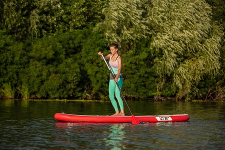 Young athletic woman doing fitness on a board with an oar on a lake. Banco de Imagens