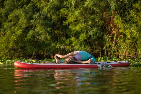 Young woman are doing yoga on a stand up paddle board SUP on a beautiful lake or river