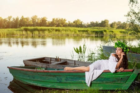 The nymph with long dark hair in a white vintage dress sitting in a boat in the middle of the river. Stock fotó