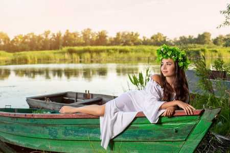 The nymph with long dark hair in a white vintage dress sitting in a boat in the middle of the river. Reklamní fotografie