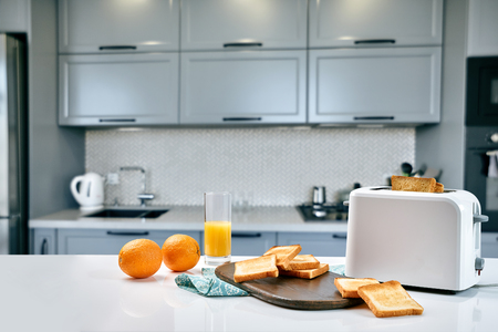 Portion of toasts on a wooden board with orange juice. Breakfast is served on a table with light blue napkin. Breakfast time