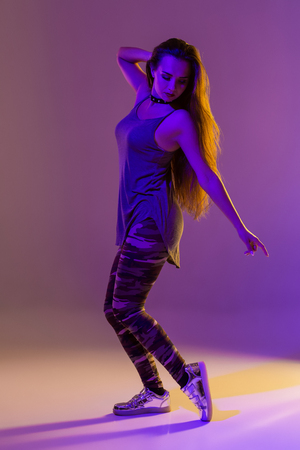 Modern style dancer posing on studio background. Color filters