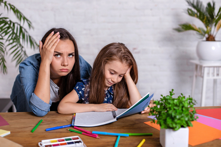 Mother becoming frustrated with daughter whilst doing homework sitting at the table at home in learning difficulties homework. 免版税图像