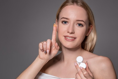 Portrait of young beautiful woman with natural makeup and contact eye lens in hand. Close-up of female model holding white lens box.