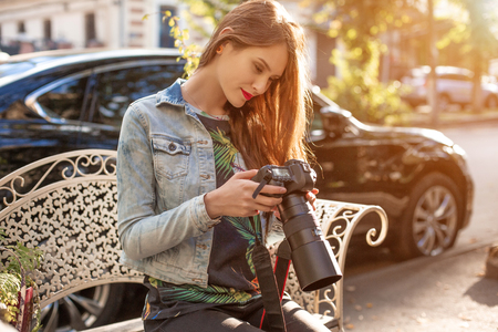 Attractive tourist woman photographer with camera, outdoor in city street. Sun flare
