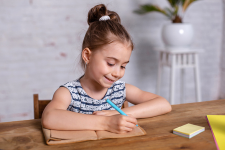 Inspired little girl at the table draw with crayons or do home work 版權商用圖片
