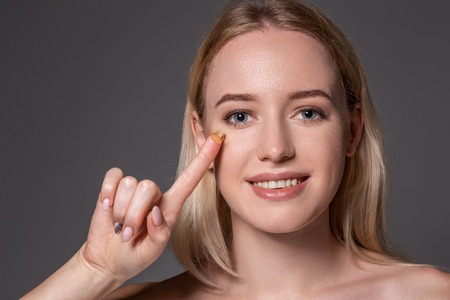 Young woman holding contact lens on index finger with copy space. Close up face of healthy beautiful woman about to wear contact lens.