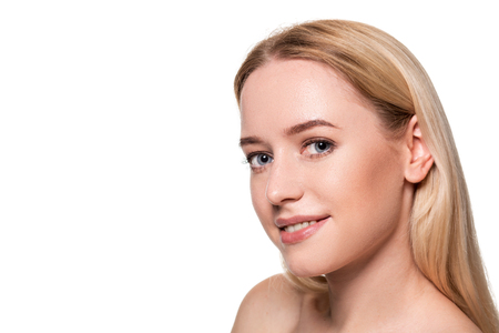 Beautiful face of young blond woman with clean fresh skin and natural make up on white background. Banco de Imagens