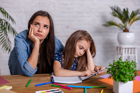 Mother becoming frustrated with daughter whilst doing homework sitting at the table at home in learning difficulties homework. Stock Photo