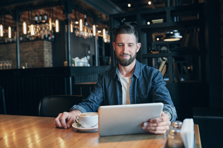 Young man drinking coffee in cafe and using tablet computer Reklamní fotografie