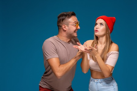 Surprised couple in casual clothes pointing with their index fingers up looking there with great astonishment isolated over blue background
