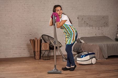 Young woman using vacuum cleaner in home living room floor, doing cleaning duties and chores, meticulous interior.