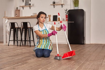 Young woman sweeping floor on the kitchen Stock Photo